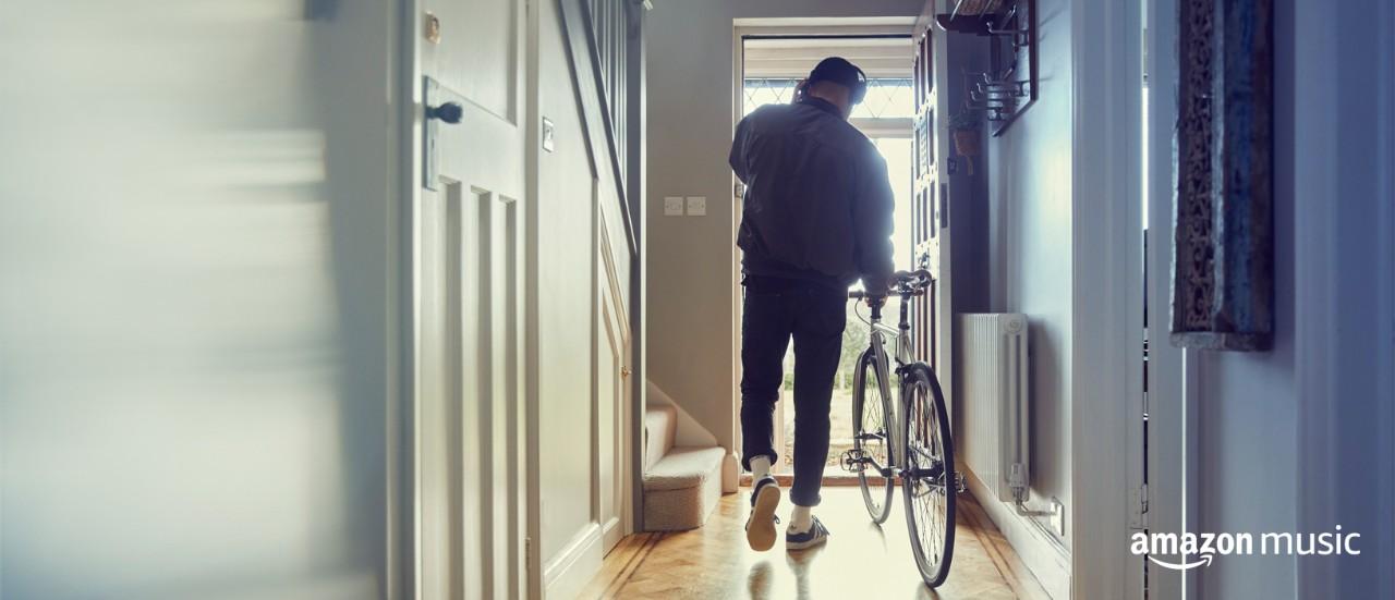 Junger Mann schiebt sein Fahrrad im Hausflur und hört dabei Amazon Music Unlimited.