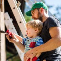 Vater streicht mit seinem Sohn das Haus