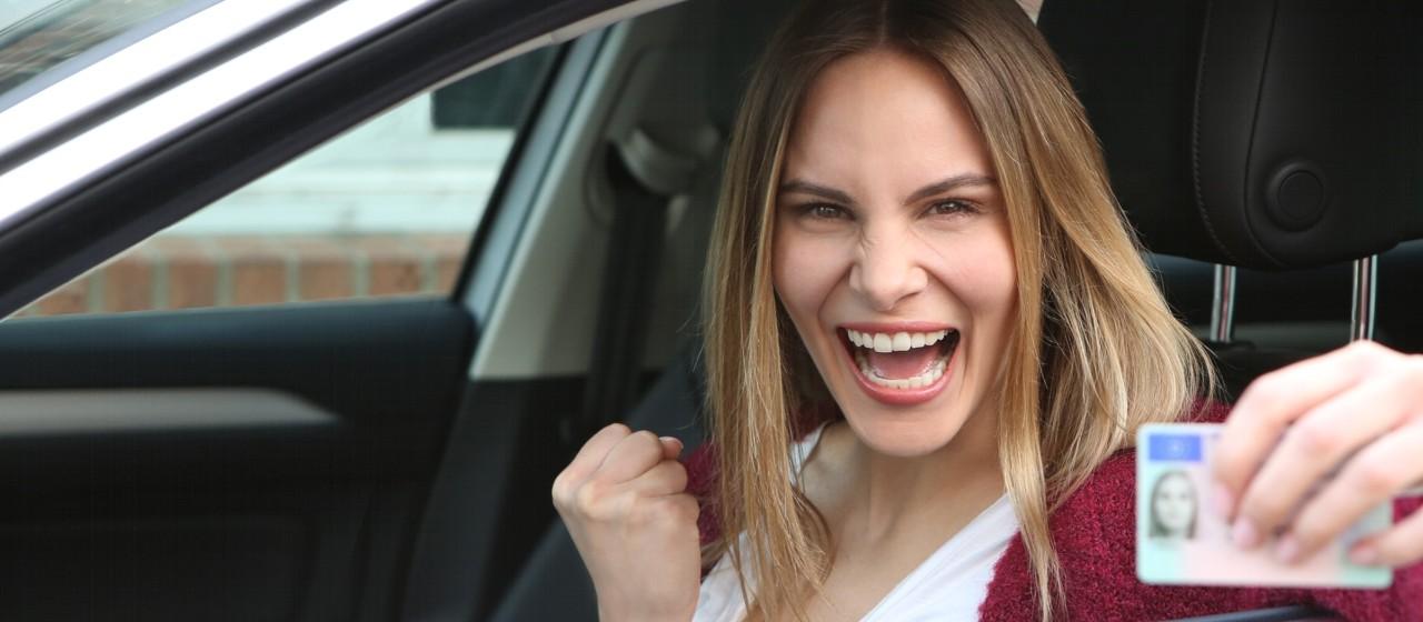 Junge Frau sitzt in ihrem Auto und zeigt ihren Führerschein.