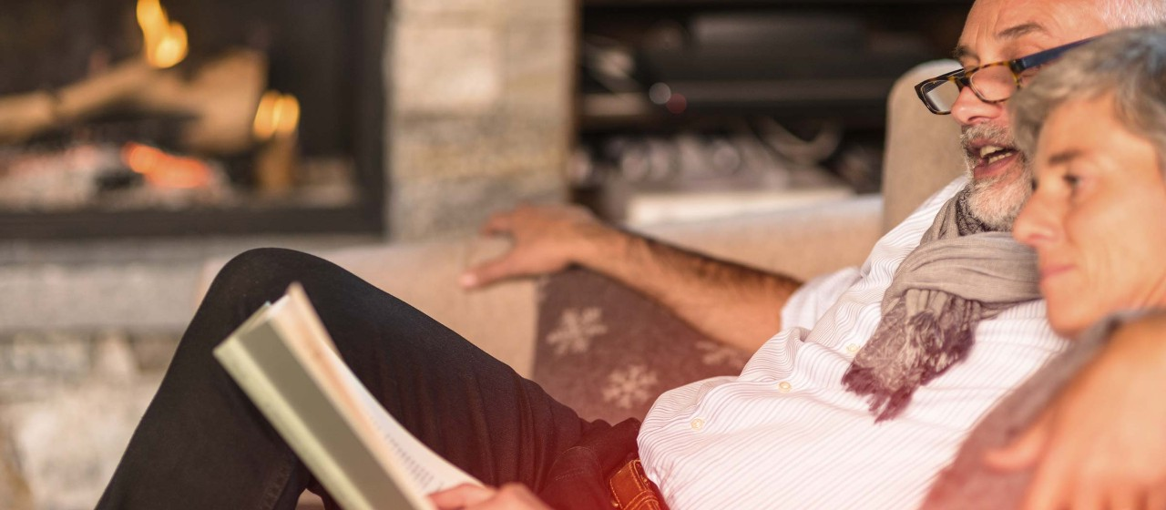 Älteres Paar sitzt auf einem Sofa und liest die Zeitung.