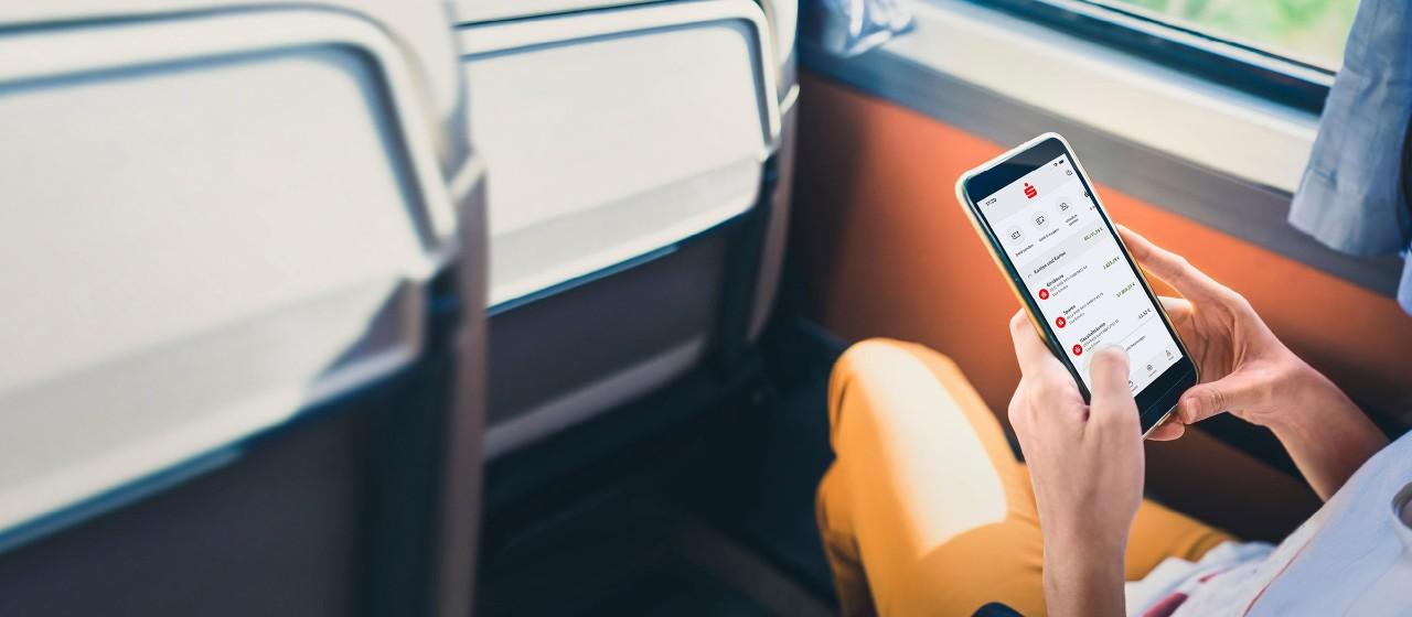 Junge Frau mit Smartphone auf einer Parkbank