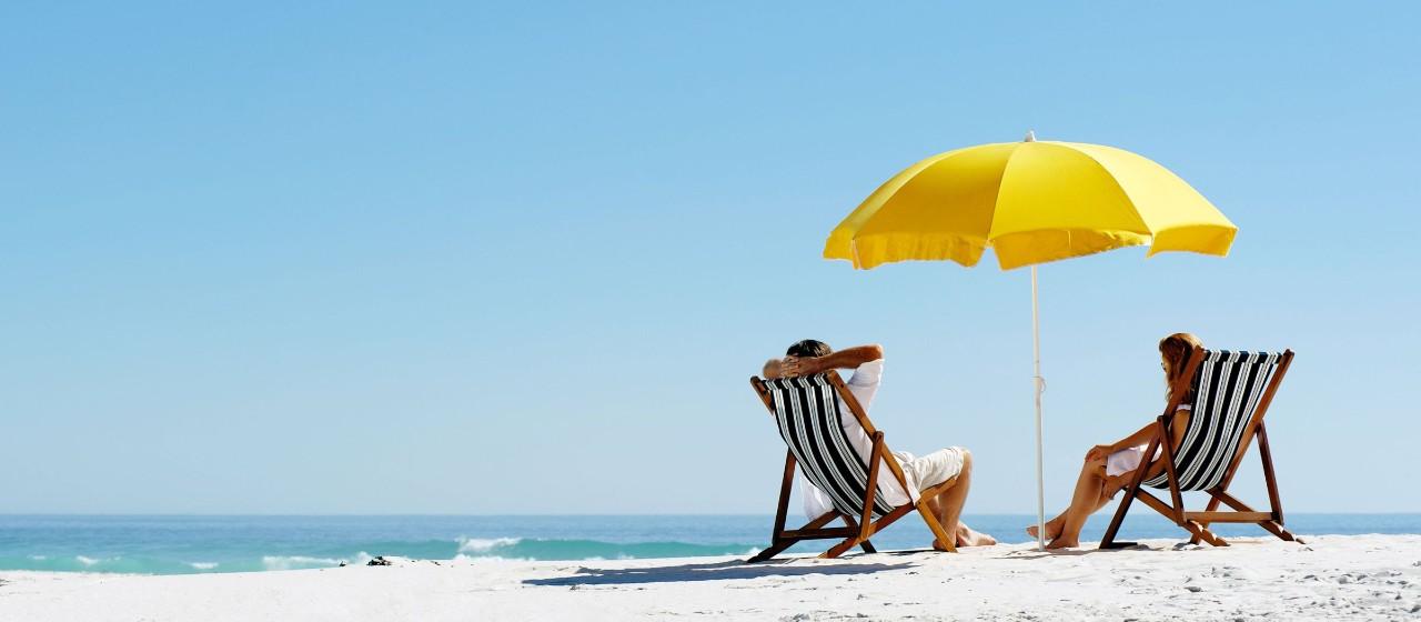 Ein Paar sitzt am Strand unter einem Sonnenschirm auf Liegestühlen.